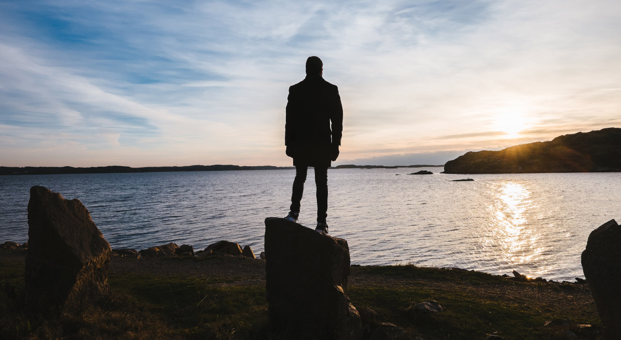 A man standing on a rock and watching sunset