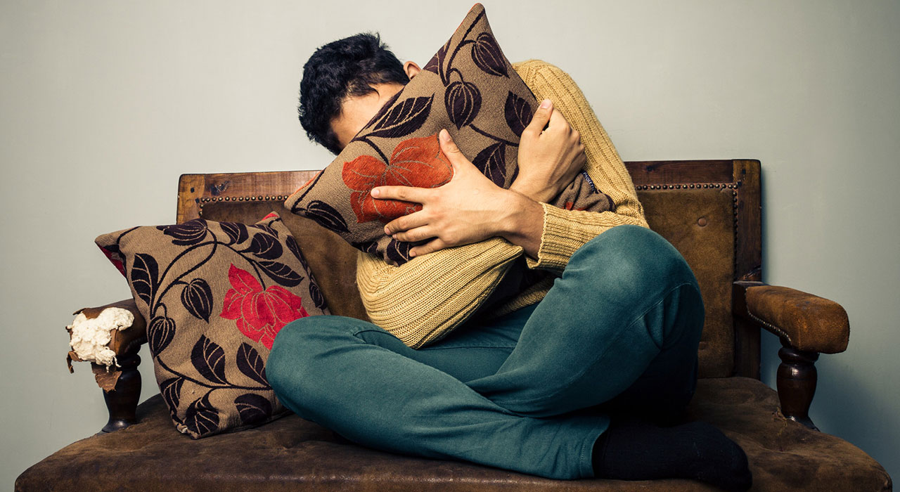 Young man is scared and hiding his face behind a cushion