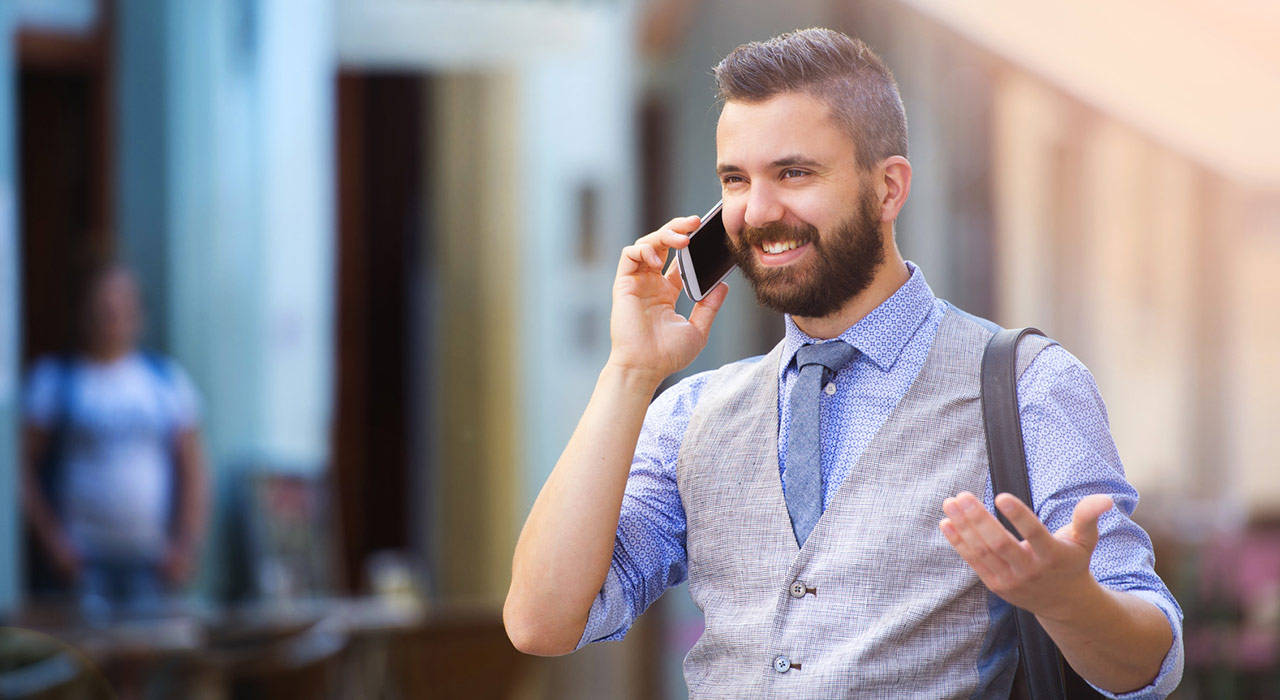 Handsome hipster with beard walking in town and calling on mobile phone