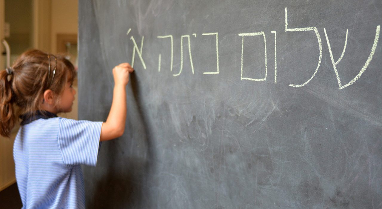 Little girl (Age 5-6) writes Hello First Grade greetings in Hebrew (Shalom Kita Alef) on a chalkboard in Israeli primary school at the beginning of the school year.