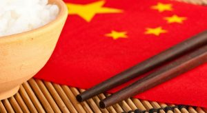 Rice bowl and chopsticks on chinese flag with bamboo mat