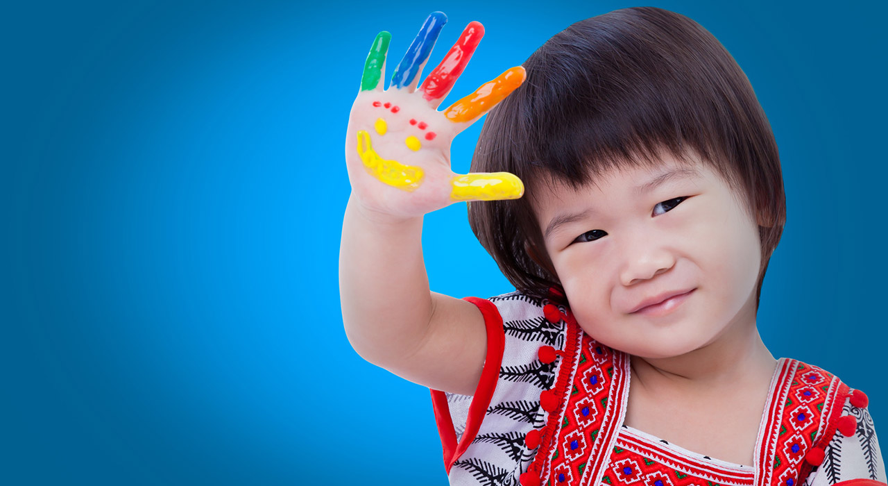 Adorable little thai girl painting her palm, colorful right hand raised up and painted with smiling face
